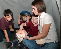 Children and adult leader inside brain dome -- with model of human brain