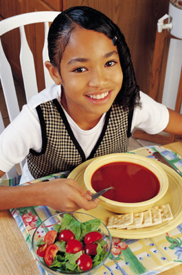 Child with soup and garden salad