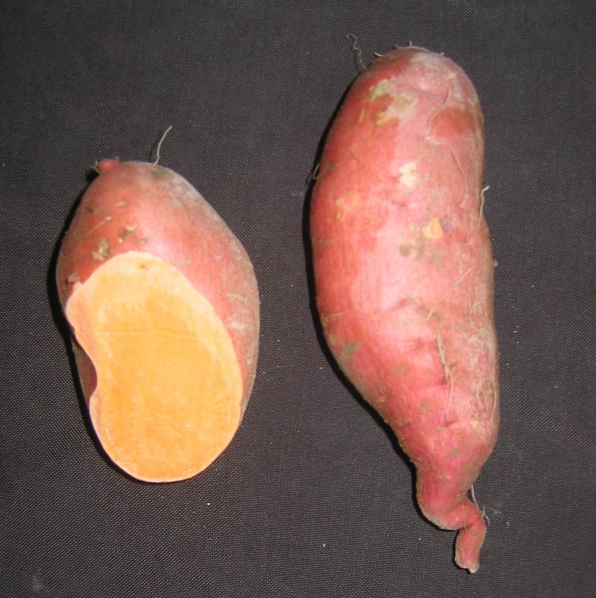 Two light rose skinned sweet potatoes. One has end cut revealing orange flesh.