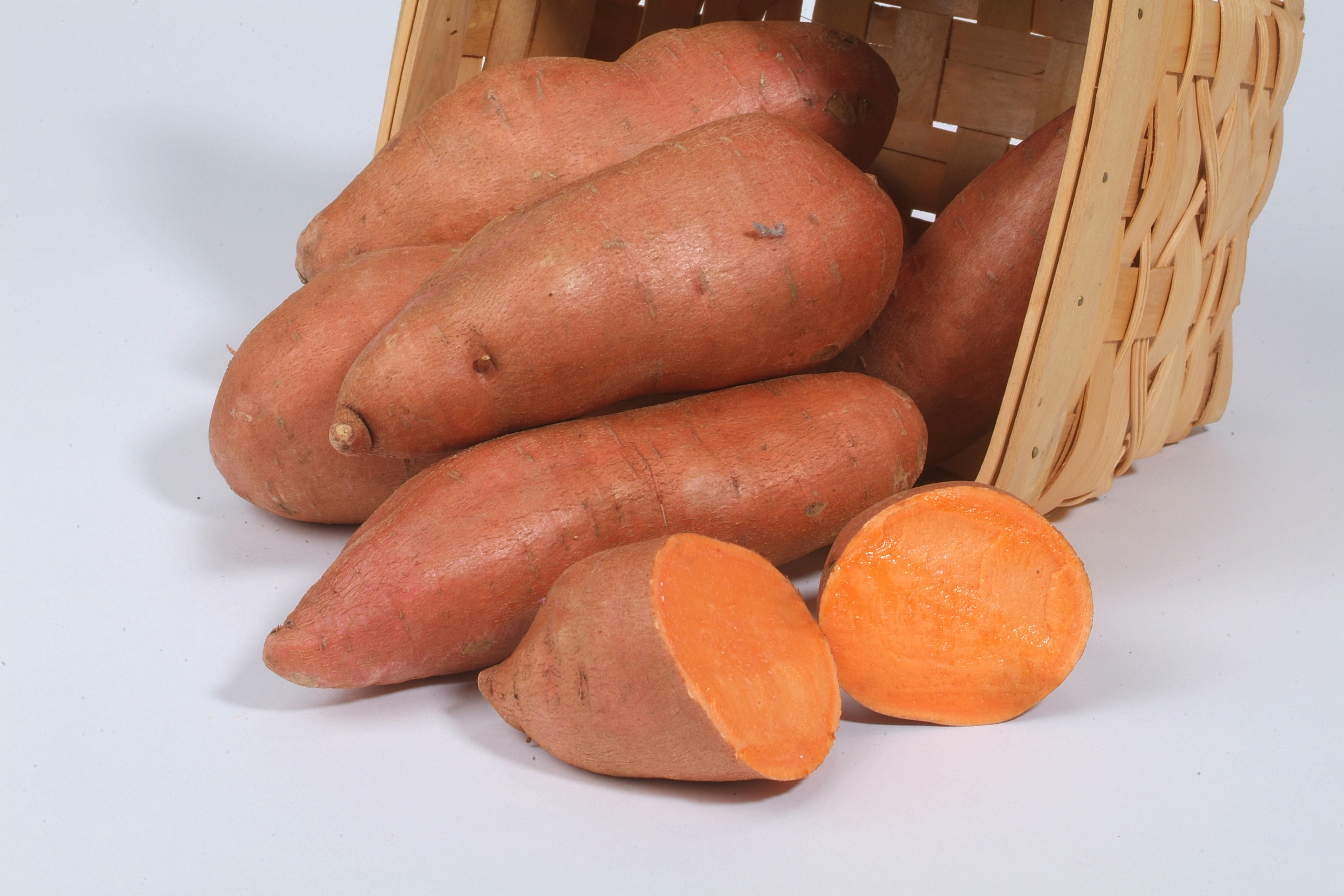 Sweet potatoes with orange skin in basket with one cut open revealing deep orange flesh.