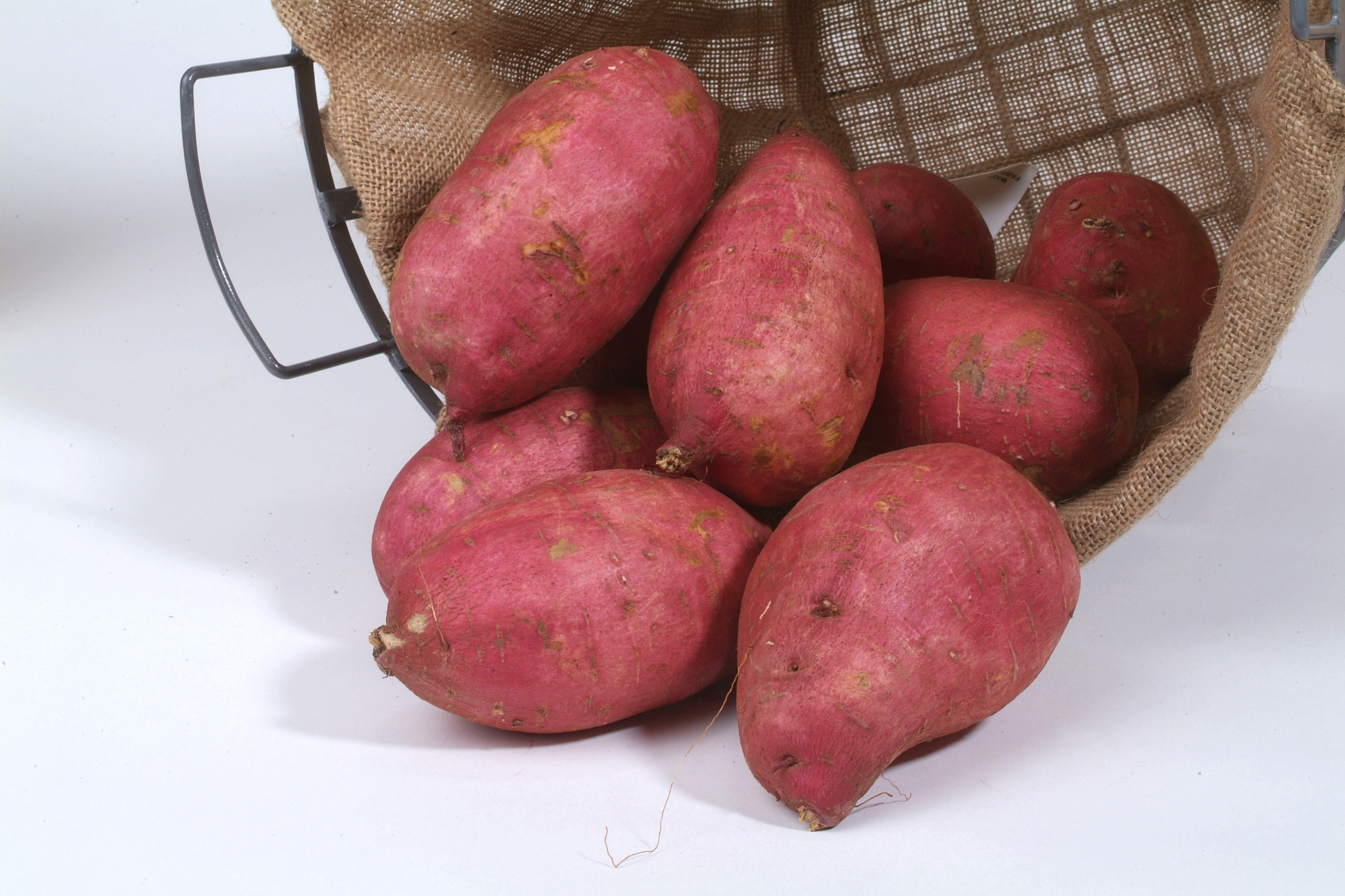 Bright red-skinned sweet potatoes in basket.