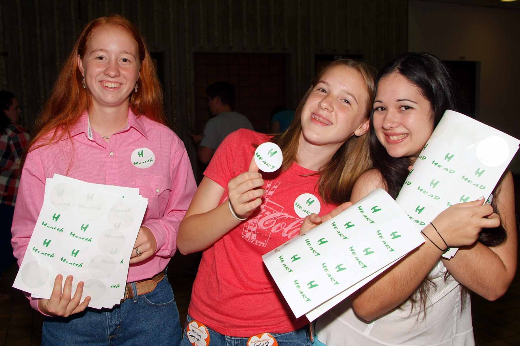 Girls with head, heart, health, hands stickers at 4-H University
