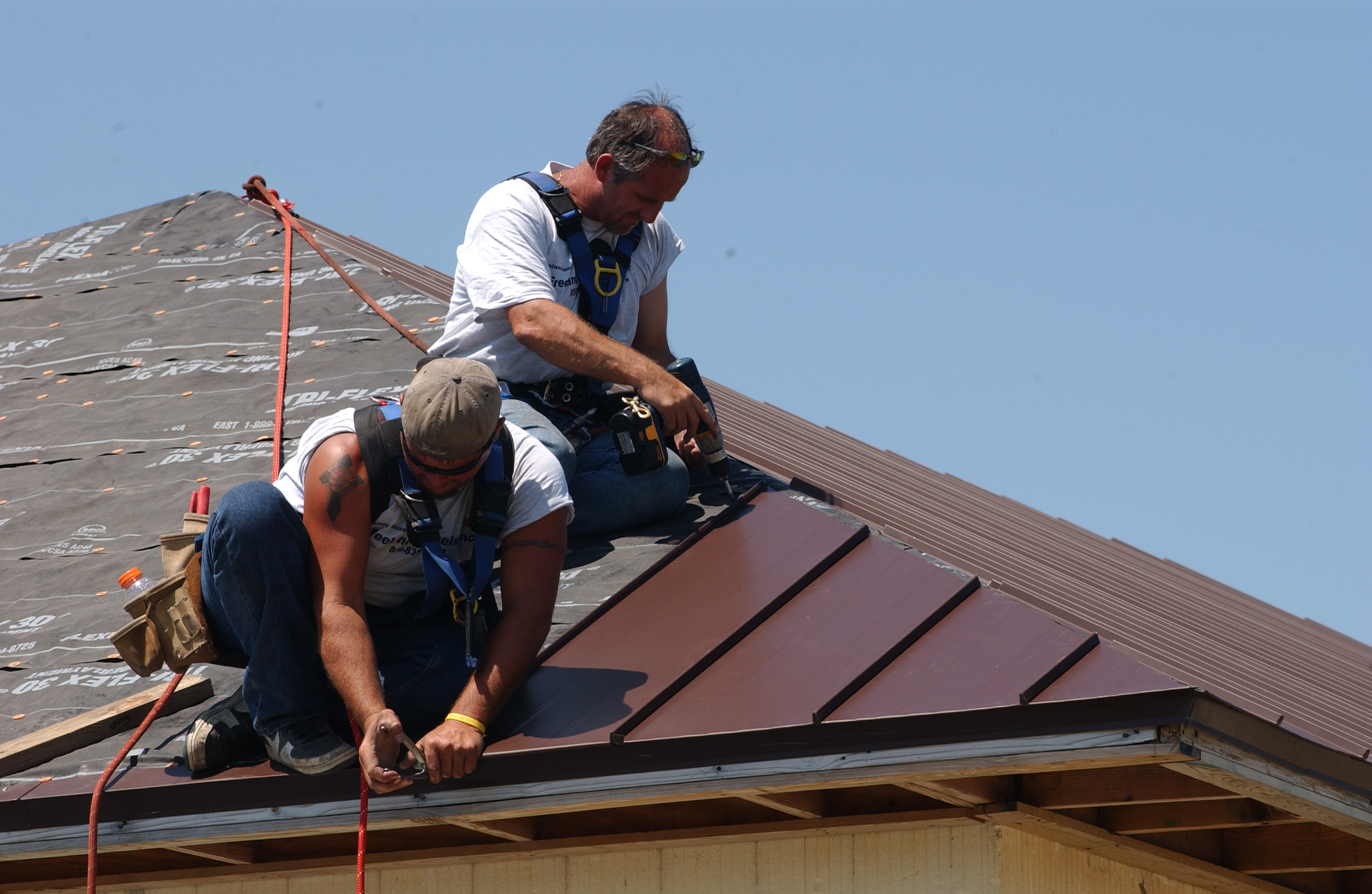 Photo of two men attaching metal roofing