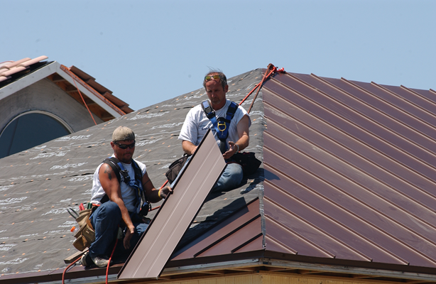 Photo of two men installing roof panel