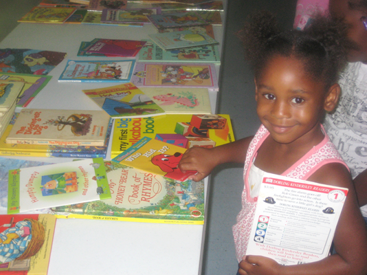 Girl selects a book in the summer reading program