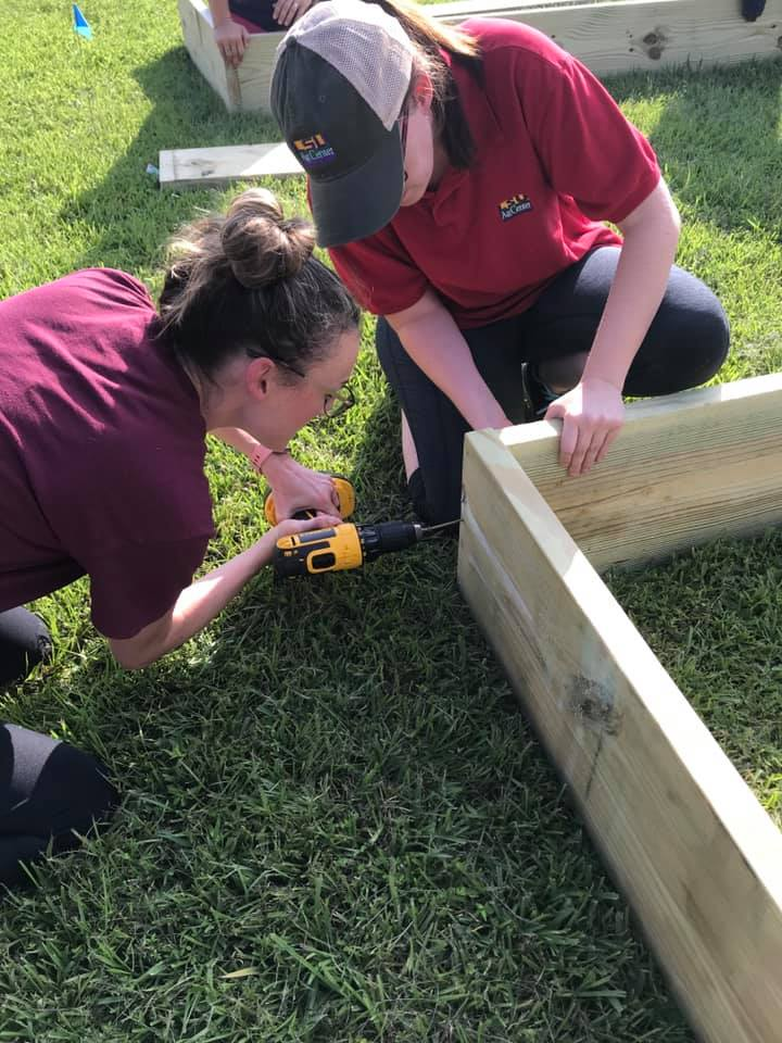 Two women fastening the edges of a garden bed box.