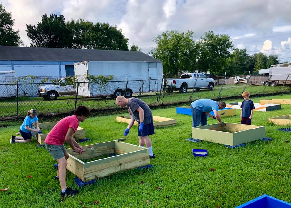 Volunteers painting garden bed boxes in a park.