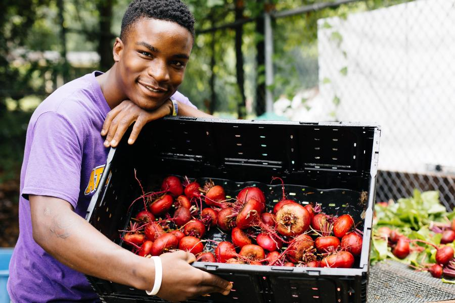 Young man holding up a box of crawfish.