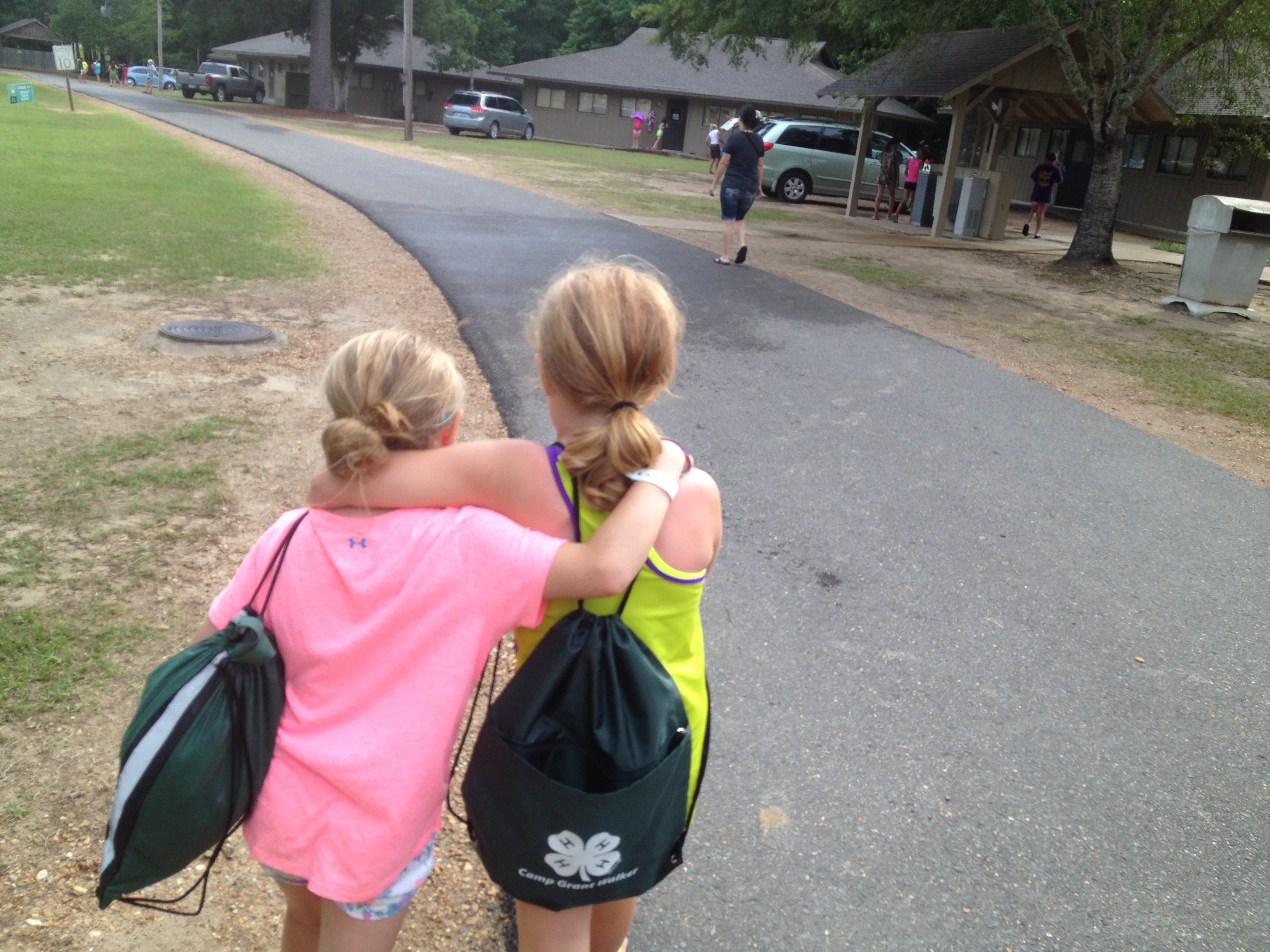 Girls with backpacks walking on the road together.