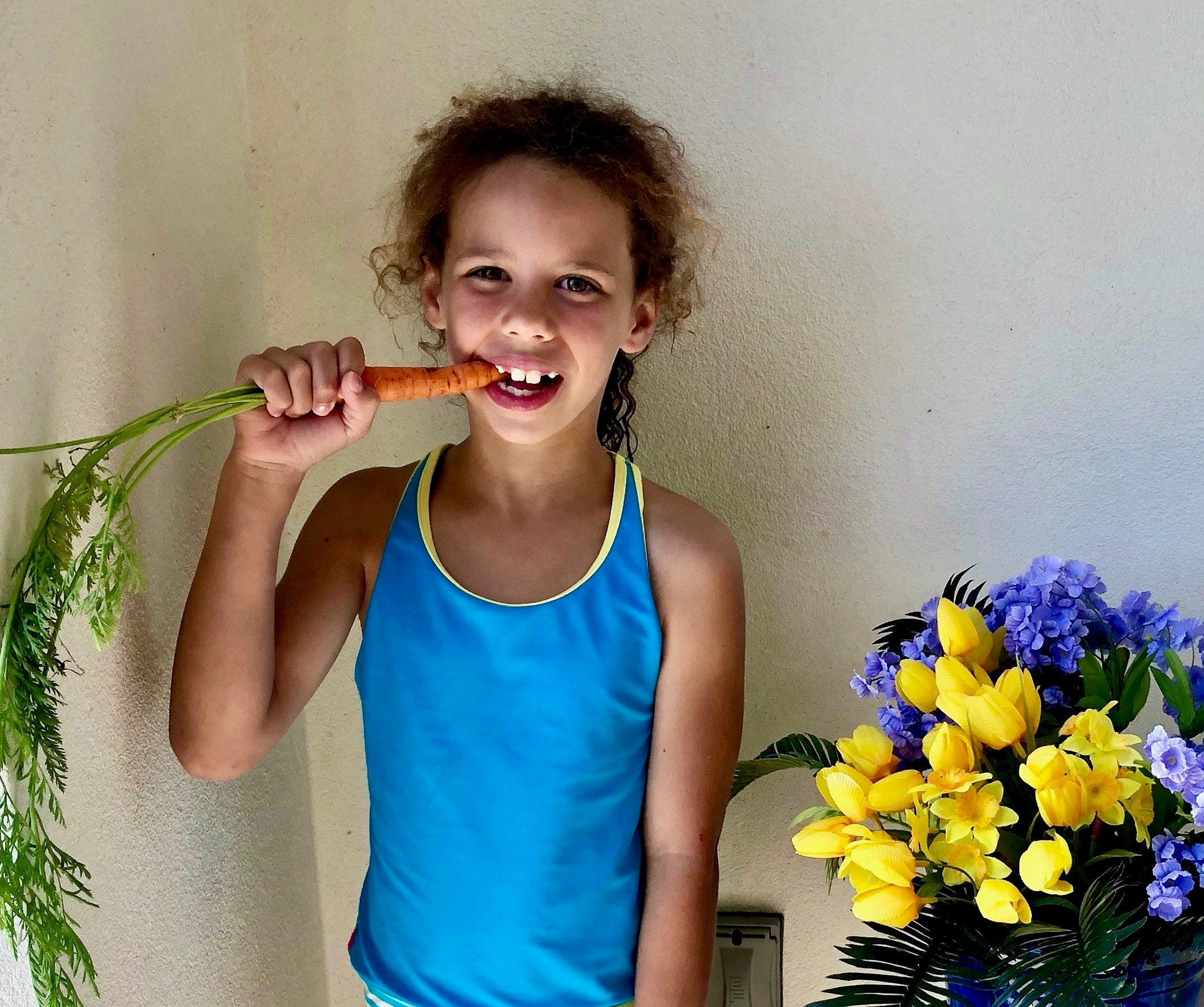 Girl eating a carrot.